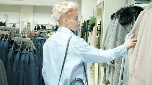 Sale, Fashion, Consumerism and People Concept - Woman Shopping Bags Choosing Clothes in Mall