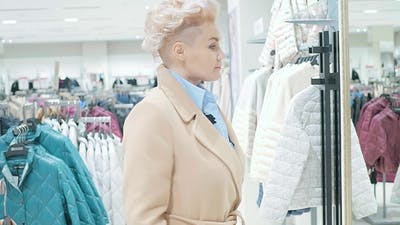 Woman Choosing Clothes in Mall or Clothing Store