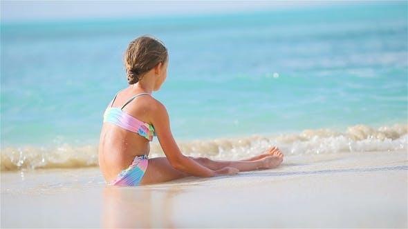Thumbnail for Adorable Little Girl Sitting on White Sand
