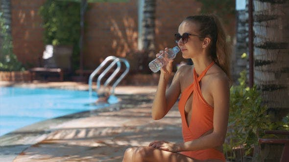 Thumbnail for Girl Drinks Water from Bottle on Sunny Day by Pool