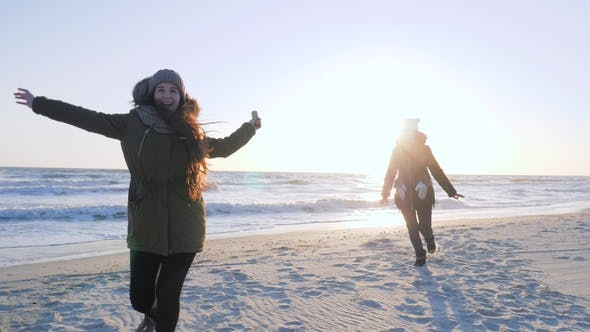 Cover Image for Cheerful Friends Have Fun and Waving Hands at Shore of Sea in Sunlight
