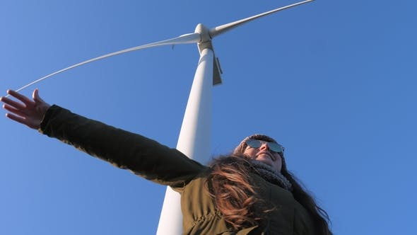 Cover Image for Cheerful Girl Having Fun and Waving Hands Under Wind Generator  Against Sky