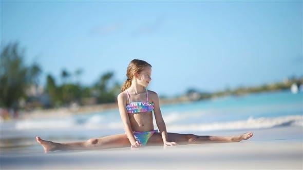 Thumbnail for Adorable Active Little Girl Sitting on Sandy Beach