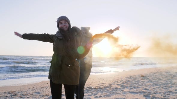 Girls with Colorful Smoke Run and Have Fun on Beach at Sea