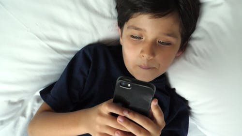 Boy Concentrating on Phone