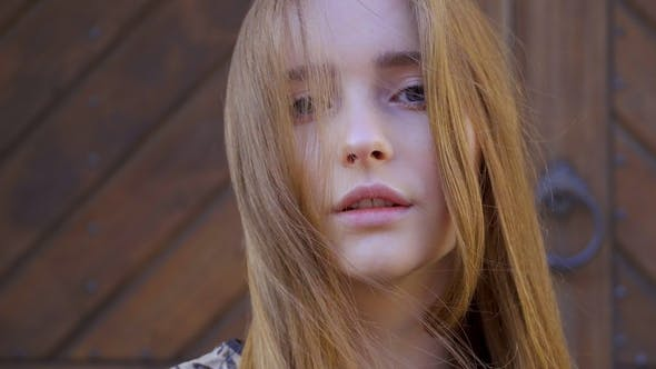 of a Girl with Long Wheat-colored Hair. Looks Directly Into the Camera, the Hair Develops the Wind