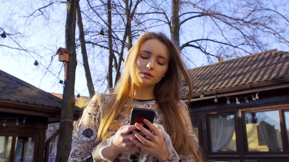 Thumbnail for A Girl Reads Messages in Her Mobile Phone