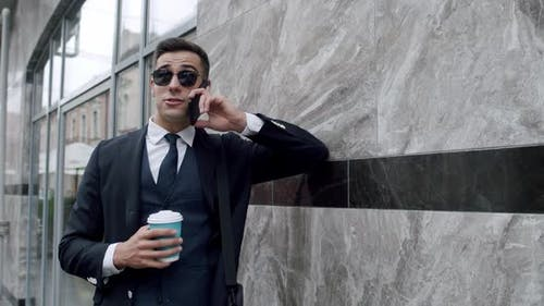 Happy Man Sunglasses Talks on Mobile Phone and Holds a Cup of Coffee Outdoor