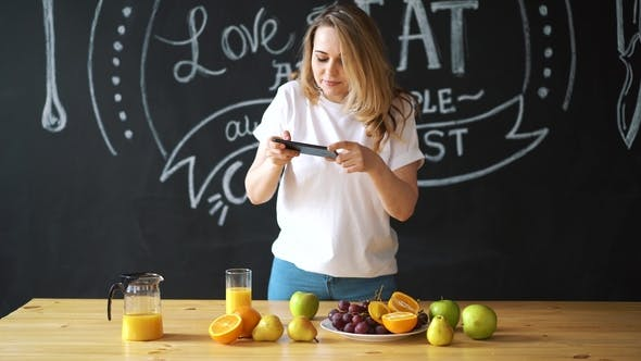 Thumbnail for Woman Taking Pictures of Healthy Food, Fruits. Orange Juice on the Table