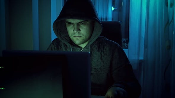 Footage of Young Male Hacker in Hoodie Working on Laptop at Home in Night. Concept of Cyber Crime