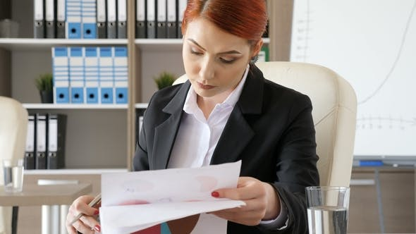 Thumbnail for Redhead Businesswoman Signing Some Papers with Charts on Them