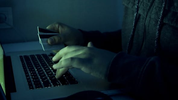 Thumbnail for Footage of Hacker Holding Credit Cards Typing Code on Laptop. Man Using Computer at Night. Perfec