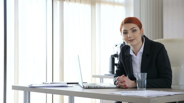 Thumbnail for Redhead Businesswoman in Suit Types at the Laptop Then Looks at the Camera and Smiles