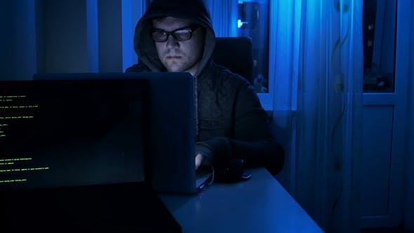 Thumbnail for Footage of Young Male Hacker Wearing Eyeglasses and Hood Working at Laptop at Night