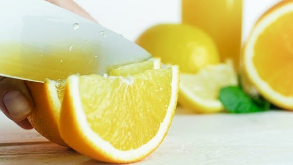 Cover Image for Footage of Hand Cutting Juicy Orange on Slices with Big Knife