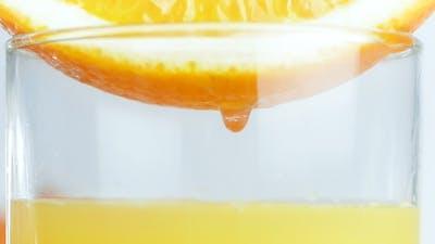 Video of Juice Orange Slice in Glass. Drops of Juice Falling Down