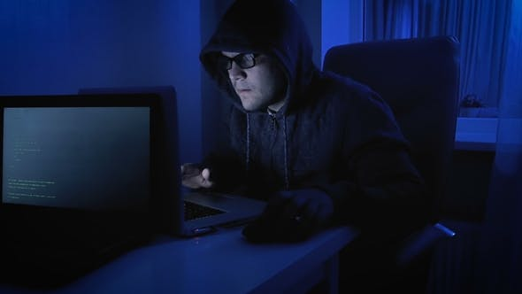Thumbnail for Funny  Footage of Male Pretends To Be Hacker. Geeky Man in Hood Working on Laptop at Night