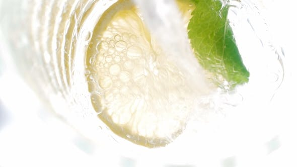Thumbnail for Footage of Pouring Cold Water in Jar with Cut Lemons, Mint and Ice Cubes