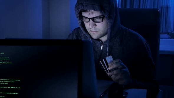 Thumbnail for Footage of Hacker Working at Night. Man in Hood Stealing Money From Credit Card