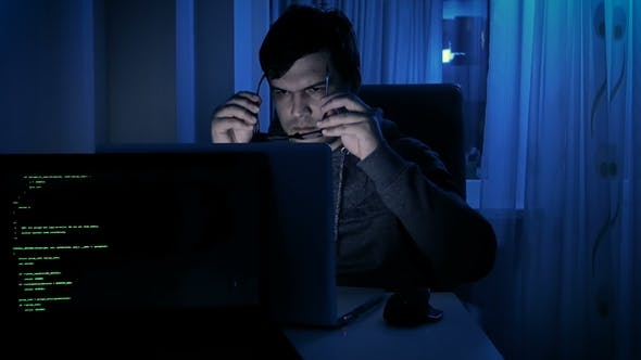 Cover Image for Footage of Young Man Wearing Hoodie and Eyeglasses Working at Computer