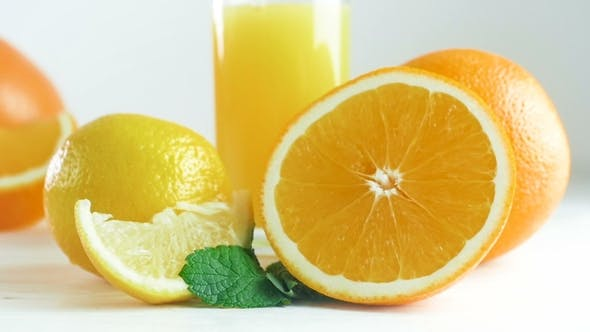 Thumbnail for Video of Camera Panning Along Assortment of Citrus Fruits and Glass of Orange Juice on White Woode
