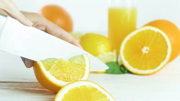 Thumbnail for Video of Young Owman Cutting Fresh Juicy Orange on White Wooden Table