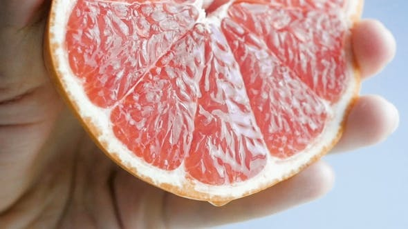 Thumbnail for Footage of Hand Squeezing Fresh Juicy Grapefruit