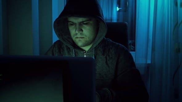 Thumbnail for Filmmaterial von jungen männlichen Hacker in Hoodie arbeiten am Laptop zu Hause in der Nacht