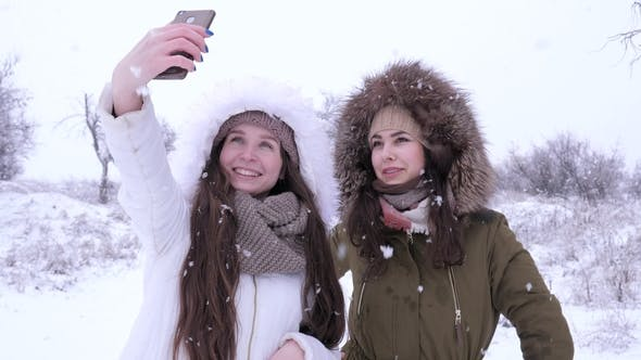 Thumbnail for Beautiful Girls Making Selfies on Cell Phone and Watching Photos during Snowfall