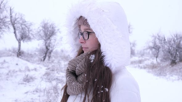 Thumbnail for Portrait of Lovely Female Spectacled Standing under Snowfall in Winter