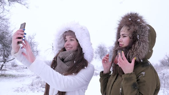 Cover Image for Girlfriends Make an Air Kiss for Photos on Gadget in Winter Time