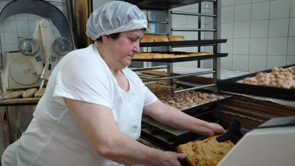 Thumbnail for Traditional Italian Bakery. A Female Baker Cuts a Big Pie Into Pieces
