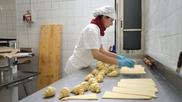 Thumbnail for Traditional Italian Bakery. A Female Baker Turns Beautiful Croissants Before Baking