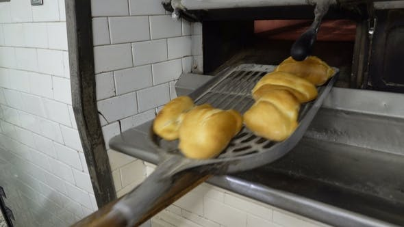 Thumbnail for Traditional Italian Family Bakery. A Female Baker Takes Hot Buns Out of the Oven