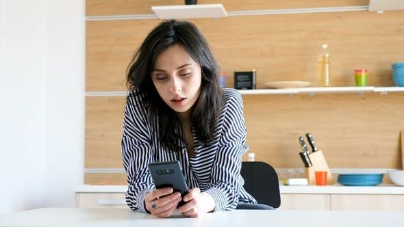 Thumbnail for Junge Frau in der Küche mit einem Smartphone in den Händen