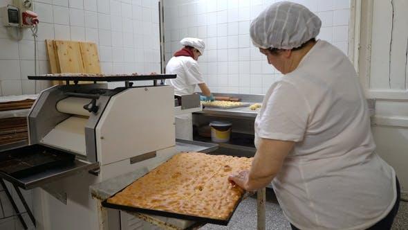 Thumbnail for Ein weiblicher Bäcker schneidet einen großen Kuchen in Stücke