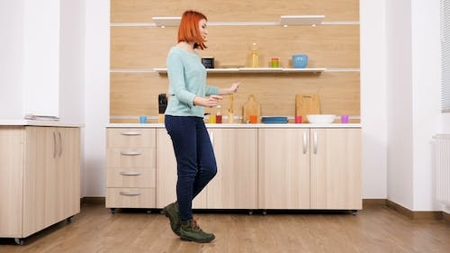 Woman in Casual Clothes Dances in the Kitchen