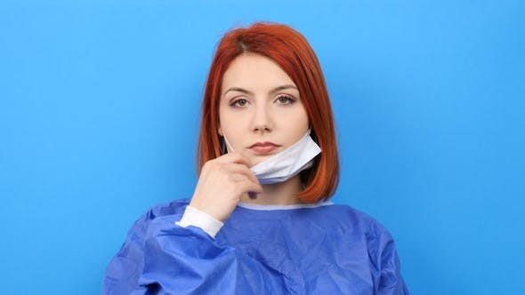 Thumbnail for Redhead Woman Wearing a Surgeon Robe Puts Her Mask on
