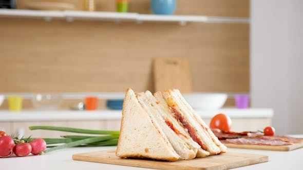 Thumbnail for Four Club Sandwiches Lying on Wooden Board