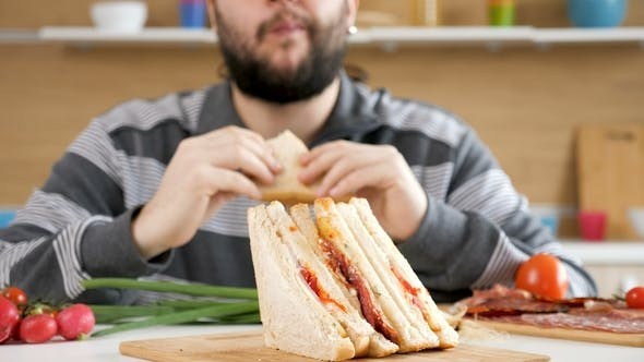 Thumbnail for Man Entering the Kitchen, Taking a Seat and Starts Eating a Sandwich