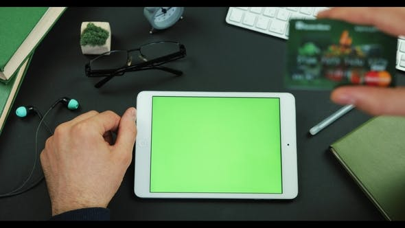 Thumbnail for Man Holds a Tablet with Green Screen and Types Information From Credit Card on a Table with Green