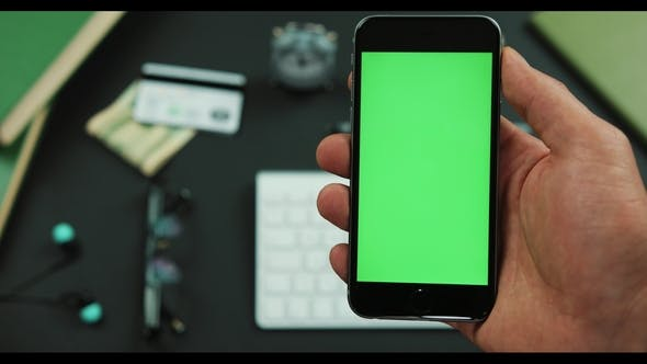 Cover Image for Man Holds a Black Smartphone with Green Screen Over a Working Table