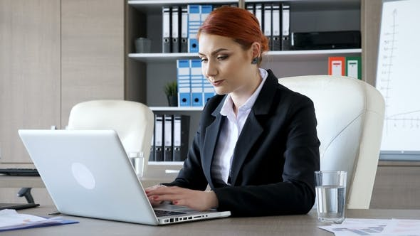 Thumbnail for Smiling Redhead Businesswoman Typing on the Laptop