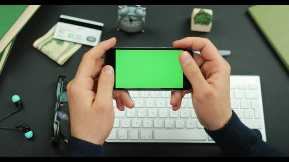 Thumbnail for Man Holds a Black Smartphone with Green Screen Over a Working Table and Scrolls Something on It