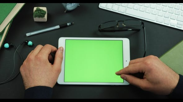 Thumbnail for Tablet with Green Screen Lies on the Working Table and Man Scrolls Something on It