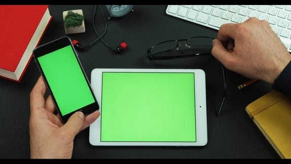 Thumbnail for Man Holds Smartphone with Green Screen Over a Table with Green Screen and Taps Something on It