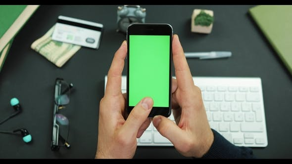 Cover Image for Man Holds a Black Smartphone with Green Screen Over a Working Table and Taps Something on It