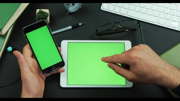 Thumbnail for Man Holds Smartphone with Green Screen Over a Table with Green Screen and Scrolls Something on It