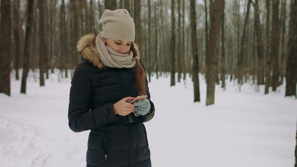 Beautiful Smiling Young Woman Using Mobile in the Winter Park