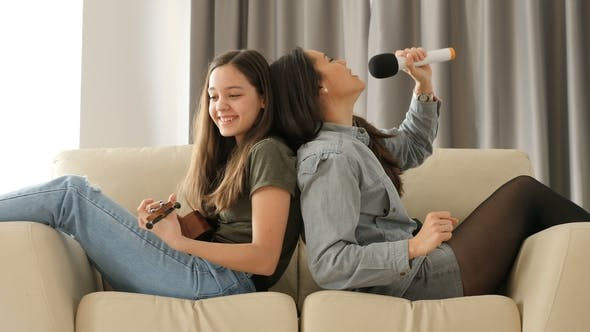 Thumbnail for Two Sisters Having Fun on the Couch, One Is Playing at Ukulele and the Other Is Singing at a